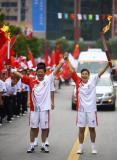 图文-奥运圣火在四川广安传递 杨利民与王建军交接