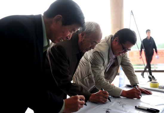 珠峰勇士成天亮(中)在西安站现场签字。