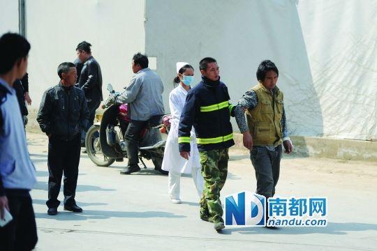 男子从塔吊下来后,消防人员搀扶着他走向救护车,手腕包扎着白纱布。