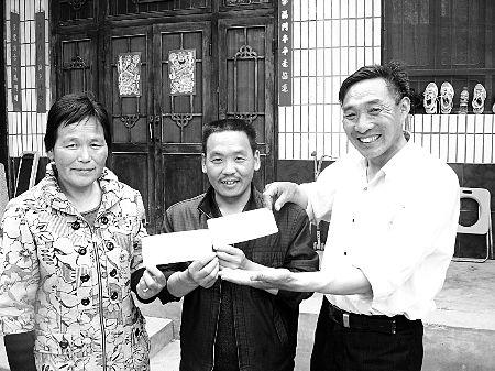 拿着王常安夫妻给他的10万元创业基金,赵利强(中)说他一定好好干。