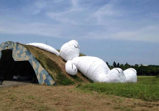 A 25.3-meter-long giant rabbit designed by Dutch artist Florentijn Hofman is displayed at an old aircraft hangar as part of the Taoyuan Land Art Festival in Taoyuan, northern Taiwan, Sept 3, 2014. [Photo/Agencies]